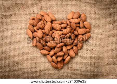 Almonds in heart shape on sack background - stock photo