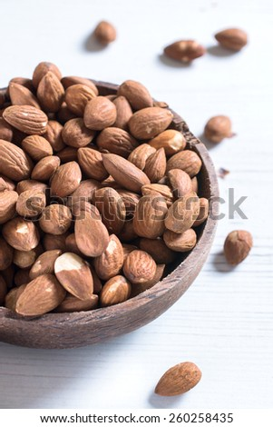 Almonds in the wooden bowl from above,selectiv focus and blank space - stock photo