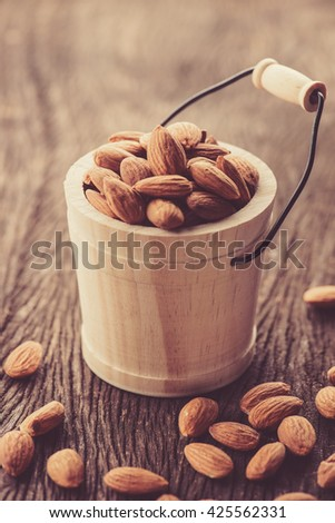 Almonds in wood bucket - stock photo