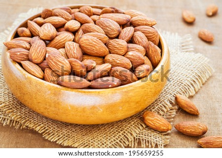 Almonds in wooden bowl on hessian mats - stock photo