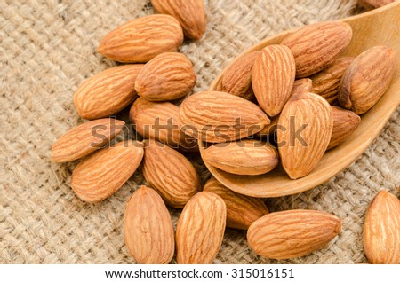 Almonds in wooden spoon on sack background. - stock photo