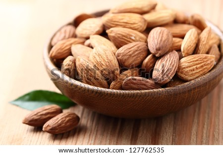 Almonds kernel in a wooden plate - stock photo