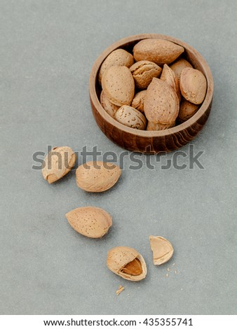 Almonds kernels and whole almonds on concrete background. Whole and chopped almond on concrete background. almond kernels and nutcracker. Selective focus depth of field. - stock photo