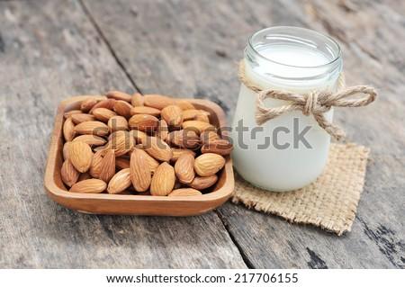 almonds milk  with almonds on dish. - stock photo