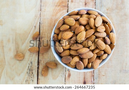 Almonds nuts on an old vintage planked wood table - stock photo