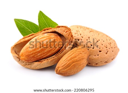 Almonds nuts with leaves close up on white background . - stock photo