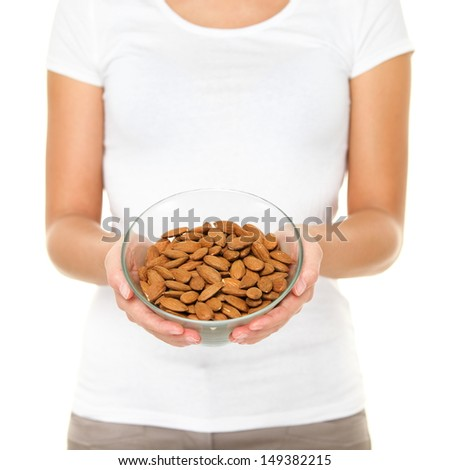 Almonds nuts - woman showing raw almond bowl. Healthy food concept in studio with hands lifting bowl of unprocessed almonds isolated on white background.
