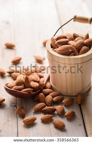 Almonds pour from wood spoon and wood bucket - stock photo