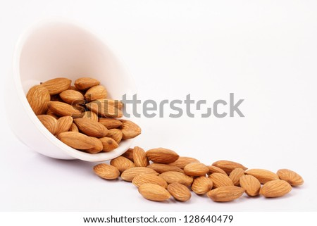 Almonds spilling on white - stock photo
