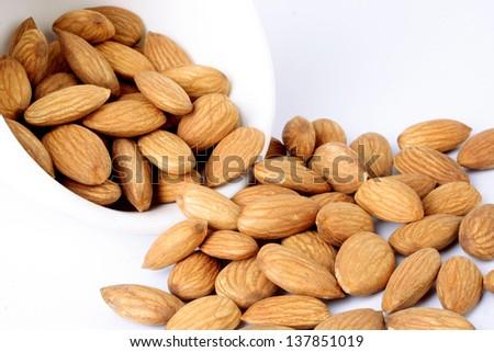 Almonds spilling on white - stock photo