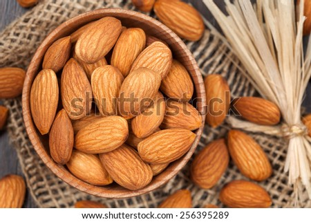 Almonds super foods in a wooden dish on vintage textile background with toning - stock photo