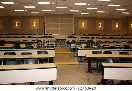 Almost empty classroom with sleeping student at the end of auditorium - stock photo