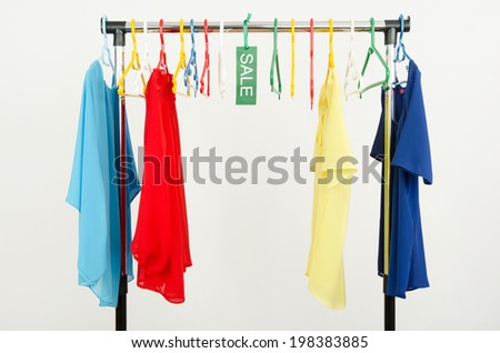 Almost empty rack of clothes and hangers after a big sale. Sale sign for summer clothes on a clearance rack with colorful summer blouses. - stock photo