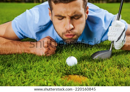 Almost in. Close-up of young golfer blowing at the ball while lying near the hole  - stock photo