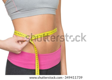 Almost perfect. Cropped closeup shot of a fitness woman with sporty toned body measuring her waist copyspace on the side - stock photo