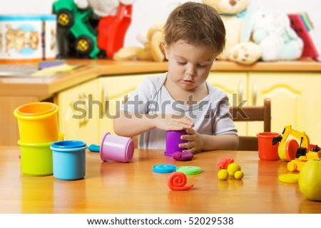 Almost 2 years old child playing plasticine in children's room - stock photo