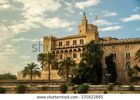 Almudaina palace with palm trees against blue sky and clouds, Palma de Mallorca, Balearic islands, Spain. - stock photo