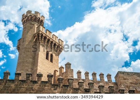 Almudaina palace with stone walls and towers against blue sky and clouds, Palma de Mallorca, Balearic islands, Spain. - stock photo