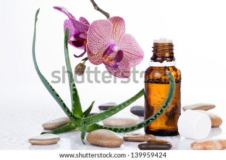 Aloe leaf and Orchid with an aromatherapy essential oil glass bottle on white