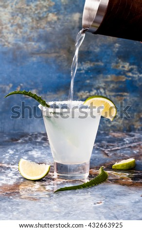 Aloe vera margarita cocktail with salty rim on marble table  - stock photo