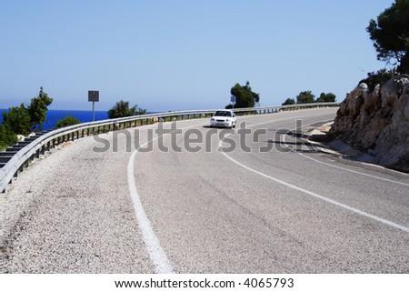 alone car on a sunny road at sea coastline - stock photo
