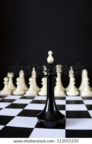 Alone chess king in front of enemy team. Unequal battle. Concept with chess pieces against black background