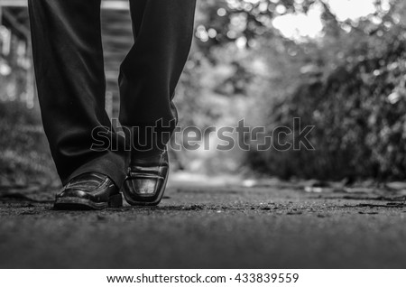 alone concept, Business man walking in park street black white, close up at he leg and ant view