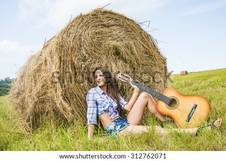 Alone Country girl playing guitar near haystack against blue sky with clouds Empty copy space for inscription Nice hot summer day Woman with smiley face hold musical instrument in hand - stock photo