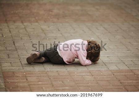 alone crying girl lying on asphalt - stock photo