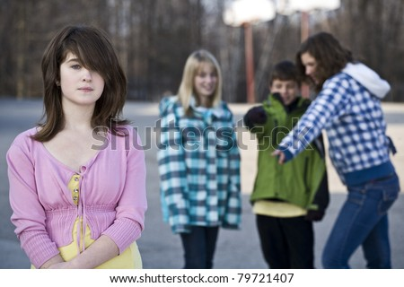 Alone in school, young girl standing away from schoolyard friends as they make fun of her behind her back - stock photo