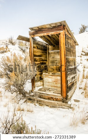 Alone in the snow stands this outhouse.  The door is missing and the structure is in an arrested state of decay. - stock photo