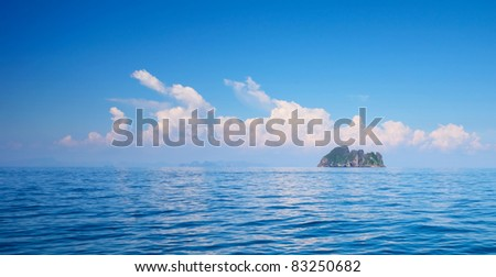 Alone island in blue sea and sky with clouds