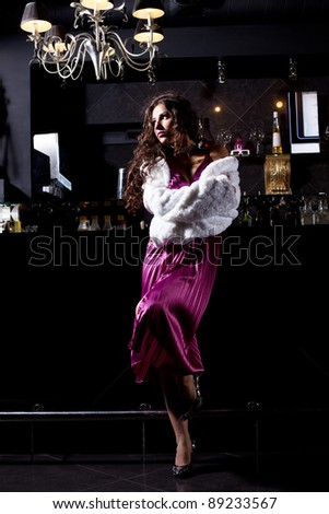 Alone luxury woman in purple dress stand at bar - stock photo