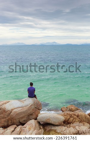 Alone man (lonely) on the rock beside the sea - stock photo
