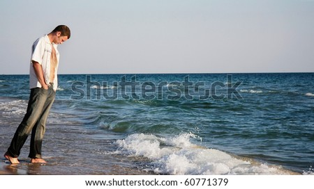 alone man on water edge - stock photo