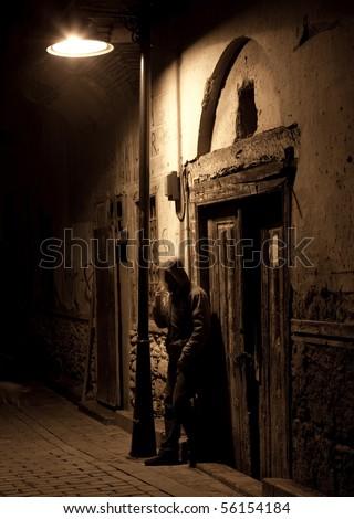 Alone man smoke under the streetlight - stock photo