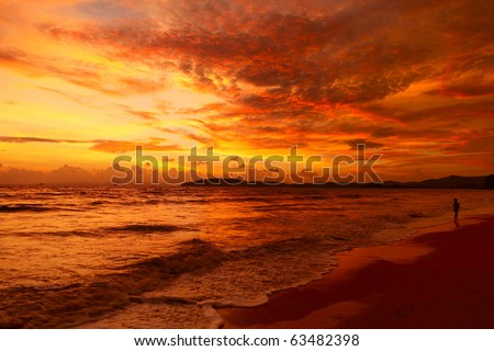 Alone man walking on beach under sunset - stock photo