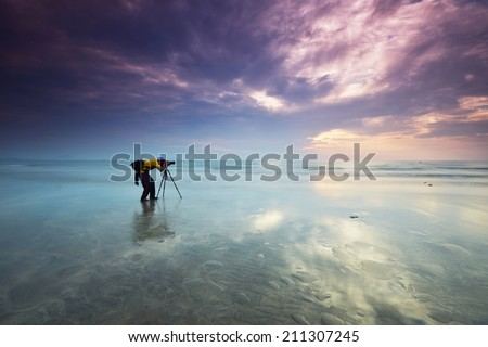 Alone nature Muslim Photographer shoots the seascape with reflection clouds - stock photo