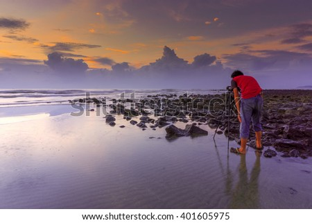 Alone nature Muslim Photographer shoots the seascape with reflection clouds.  - stock photo