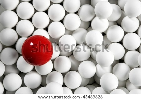 Alone one billiard red ball between little white table football balls - stock photo