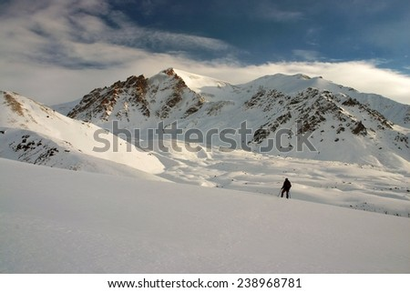 Alone ski tourist in the mountains - stock photo