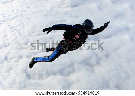 Alone skydiver is above the clouds.