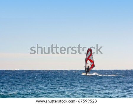 Alone surfer on board in sea with clear blue sky - stock photo