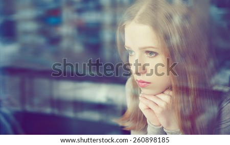 alone thoughtful sadness girl is sad at the window - stock photo