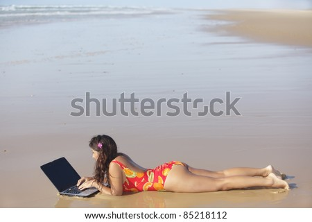 alone woman working with laptop on wild beach - stock photo