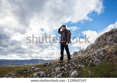 Alone young hiker enjoying the view over the mountain - stock photo