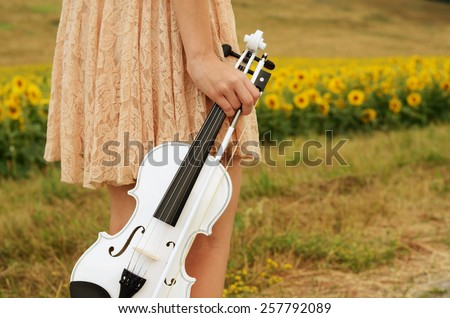 Alone young woman holds violin and bow - stock photo