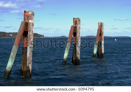 Along the waterfront in Portland Maine three weathered pilings line a public boat launch - stock photo