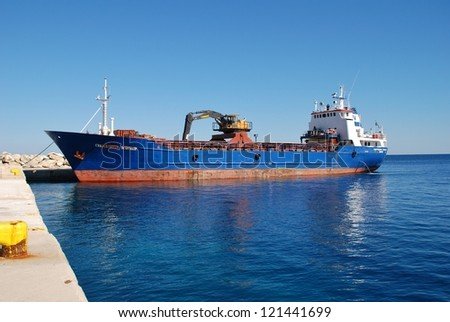 ALONISSOS, GREECE - SEPTEMBER 22: Freight ship Evagelistria Skopelou unloads at Patitiri harbour on September 22, 2012 in Alonissos island, Greece. The ship was built in Norway in 1971.
