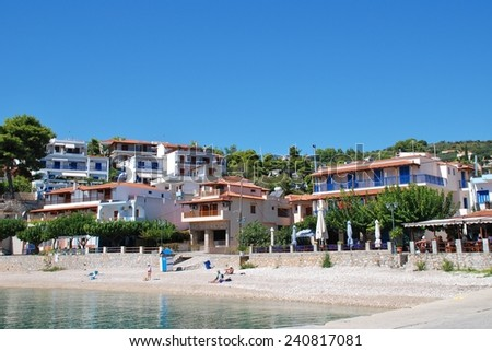 ALONISSOS, GREECE - SEPTEMBER 23, 2012: People sit on the shingle beach at Rousoum on the Greek island of Alonissos. Rousoum was once the centre of the islands wine exporting trade. - stock photo